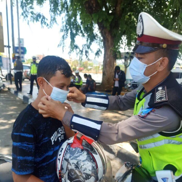 Anggota Satlantas Polres Pangkep memakaikan masker kepada pengendara sepeda motor dalam Operasi Zebra 2020